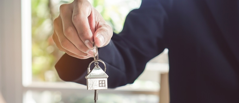 A Realtor Giving a Key from a House to a Buyer