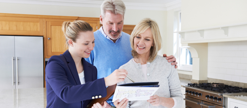A Realtor Showing Prospects a Property Brochure