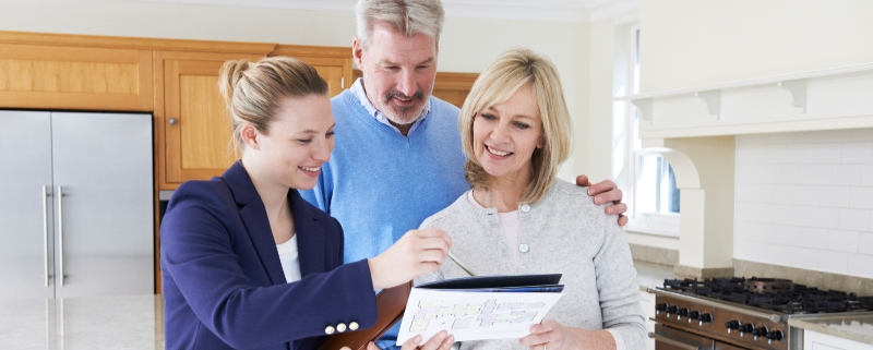 A Realtor Showing Mature Prospects a Property Brochure